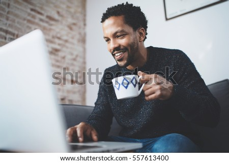 Cheerful African man using computer and smiling while sitting on the sofa.Black guy holding ceramic cup in hand.Concept of young business people working at home.Blurred background.Selective focus