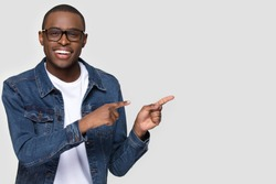 Cheerful african man wearing glasses jean jacket having white snow smile pointing fingers aside at copy space for your text advertisement, advertise teeth whitening or eyewear store good offer concept