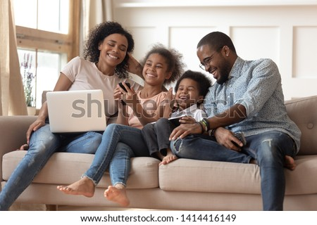 Cheerful african parents and kids laugh use devices together sit on sofa, tech addicted family with children hold laptop phone digital tablet having fun with gadgets at home, technology dependence