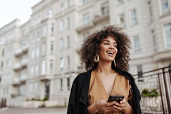 Cheerful African woman holds smartphone. Curly brunette lady in brown blouse and black coat smiles and walks outdoors.