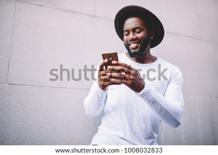 Cheerful afro american guy in stylish wear viewing photos in social networks on mobile enjoying free time outdoors, happy dark-skinned man watching funny video on smartphone near publicity area
