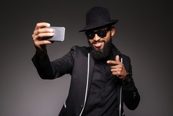 Cheerful afro american man in trendy cloth taking selfie photo on smartphone over black background