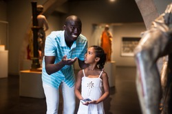 Cheerful Afro father and daughter standing at hall of museum and looking at exhibits of medieval sculpture