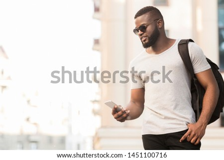 Cheerful afro man in stylish wear viewing photos in social networks enjoying free time outdoors, panorama, copy space #1451100716