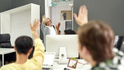 Cheerful aged woman, senior intern waving, saying goodbye to her young colleagues while leaving office after first day at work, Selective focus, Web Banner
