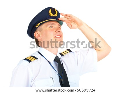 Cheerful airline pilot wearing uniform with epaulets and hat looking upwards, standing isolated on white background.