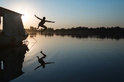 Cheerful and carefree child jumping into the water from a boat at sunset