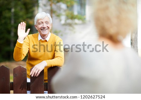 Cheerful and friendly mature man waving hand to his neighbour while standing by fence