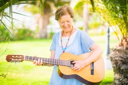 Cheerful and happy old aged senior caucasian woman smiling and having fun playing a  guitar and dong music in outdoor park leisure activity - retired happy people with interests enjoying new life