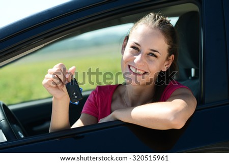cheerful and happy young woman in car showing car keys