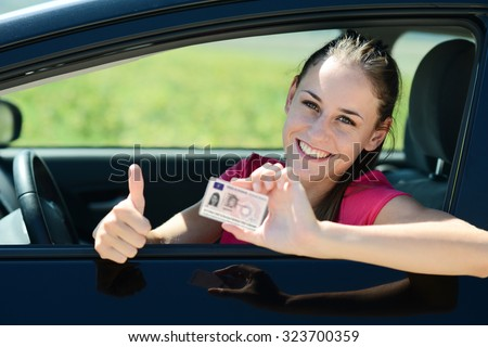 cheerful and happy young woman in her car showing her new driving license