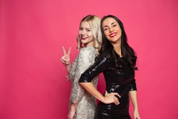 Cheerful and joyful girlfriends. Two happy young beautiful smiling girlfriends in little black dresses posing and having fun on a pink background.