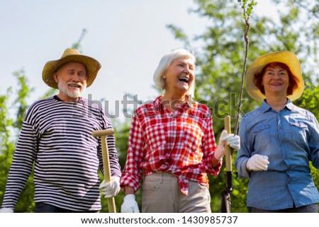 Cheerful and positive. Cheerful and positive retired man and women heading to plant trees #1430985737