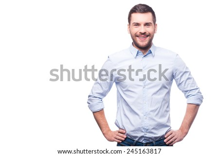 Cheerful and stylish. Handsome young man in shirt looking at camera and holding hands on hips while standing against white background