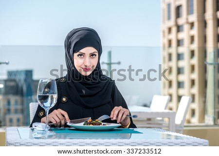 Cheerful Arab clients in the restaurant. Arab women in abaya sitting in a restaurant and eat delicious food. Middle Eastern woman sitting in a hijab in resorane.