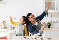 Cheerful arab father and little daughter having fun while baking together in kitchen, happy middle eastern dad and child singing and fooling, using spatula and whisk as microphones, copy space
