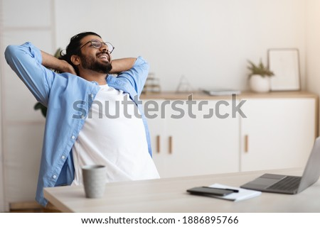 Cheerful Arab Freelancer Guy Leaning Back In Chair, Relaxing After Successful Work, Sitting At Table With Laptop Computer In Home Office, Millennial Man Resting At Workplace With Hands Behind Head Photo stock ©