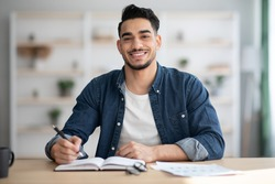 Cheerful arab guy in casual sitting at workdesk, taking notes and smiling at camera, office interior, copy space. Happy young middle-eastern man sitting at table with papers, studying, home interior