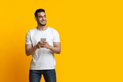 Cheerful arab guy with smartphone looking at copy space and smiling, yellow studio background, panorama. Positive middle-eastern young man chatting on mobile phone, using new application