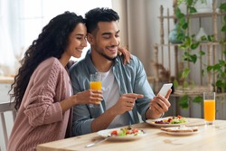 Cheerful Arab Spouses Using Smartphone While Eating Breakfast In Kitchen, Happy Middle Eastern Couple Enjoying Tasty Morning Meal, Shopping Online Or Checking Social Networks On Cellphone, Free Space