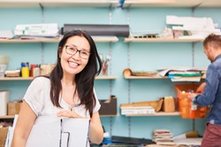 Cheerful Asian art student buys painting materials in the art supplies shop