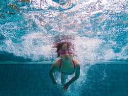 Cheerful Asian little girl diving and swimming in pool on summer vacation.