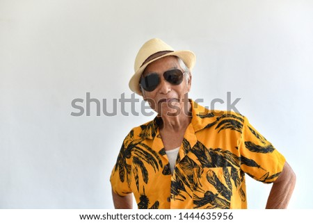 Cheerful asian senior old man, Confident and smiling elderly people with sunglasses in colorful hawaii shirt, Happy retiree citizen and travel concept.