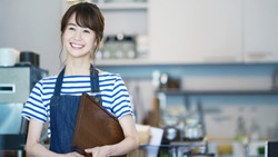 Cheerful asian waitress in cafe.
