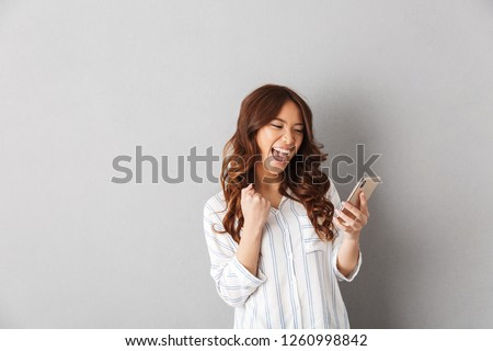 Cheerful asian woman standing isolated over gray background, holding mobile phone, celebrating Foto d'archivio ©