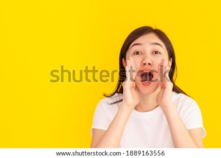 Cheerful Asian young woman shouting - yelling with hand close up on studio yellow background. Happy beautiful girl using hand at her mount while screaming, woman speaking louder. Advertising concept. Foto stock ©