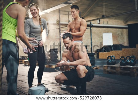 Cheerful athletic adults talking while applying talcum powder to hands before doing intense workouts requiring a firm grip ストックフォト ©