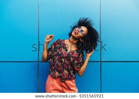 Cheerful attractive afro american girl enjoying spending time outdoors, dancing, wearing sunglasses, dressed in colorful blouse and pants, looking at the sky. On blue wall background