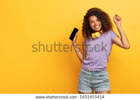 Cheerful attractive girl with curly hair, dark skin, enjoys cool songs downloaded from online website, wears headphones, holds modern smart phone, moves in music rhythm over yellow studio wall #1431455414