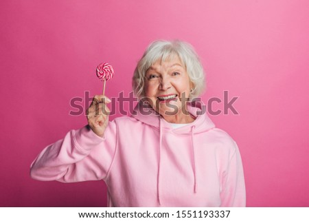 Cheerful attractive senior female model on picture. Hold lollipop in hand and smile. Beautiful old woman in stylish modern hoody. Isolated over pink background