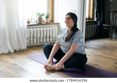 Cheerful attractive young overweight woman in activewear choosing healthy lifestyle, sitting on mat with hands on bare feet, doing butterfly yoga exercise, stretching thighs. Body shape and activity stock photo