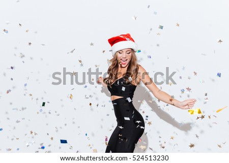 Cheerful attractive young woman in santa claus hat dancing and having fun over white background