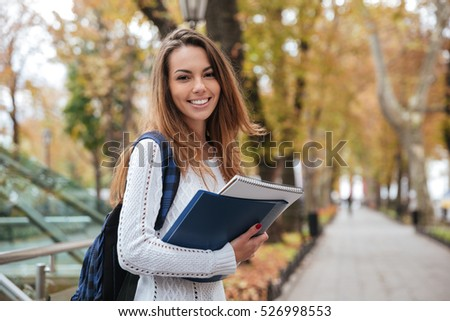 Cheerful attractive young woman with backpack and notebooks standing and smiling in park