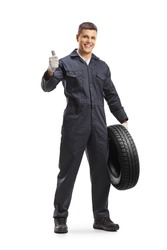 Cheerful auto mechanic worker holding a car tire and showing thumbs up isolated on white background