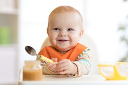 Cheerful baby child eats food itself with spoon. Portrait of happy kid boy in high chair.
