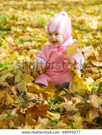 Cheerful baby girl playing with autumnal leaves