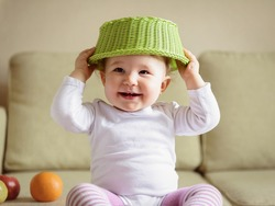Cheerful baby girl plays with fruits at home. One-year-old child puts a fruit basket on his head like a hat. A funny smiling baby is naughty. Nice portrait of a cute playful baby.