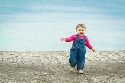 Cheerful baby girl walks on beach. One-year-old child runs on old sea pier. Cute baby is playing outdoor. Little happy baby in denim overalls on neutral background. Portrait of funny toddler outside.