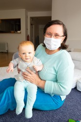 Cheerful babysitter in face mask playing with baby in home interior, sitting on floor and holding child. Pandemic and babysitting concept