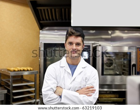 Cheerful baker standing in his kitchen with baguettes and stove in the background