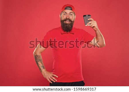 Cheerful barista. Man bearded hipster red cap uniform hold paper coffee cup. Barista recommend caffeine beverage. Barista job position. Coffee shop staff wanted. Barista prepared drink for you.