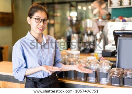 Cheerful barista showing coffee varieties and offering to buy tasty coffee. Positive young Asian restaurant manager presenting coffee. Drink establishment concept #1057496951
