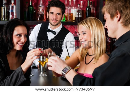 Cheerful barman behind counter with young friends at cocktail bar