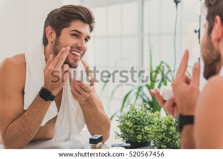 Cheerful beaded guy caring of his skin