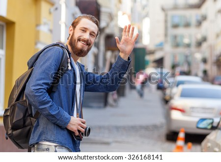 Cheerful bearded guy is traveling across city. He is standing and waving arm with joy. The tourist is standing and smiling. He is holding camera and backpack