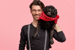 Cheerful bearded male has toothy smile, glad to pose at camera with his pedigree dog, likes pets, dressed in fashionable black shirt and suspenders, isolated over pink wall. Happy man with animal